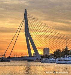 Een sensationele zonsondergang in Rotterdam. De lucht achter de beroemde Erasmusbrug en het water van de Koningshaven kleuren Oranje alsof het Koningsdag is. Rechts zien we de kade van het Noordereiland; op de achtergrond is verder nog dat andere icoon van Rotterdam te zien: de Euromast.