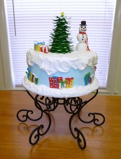 Chocolate cake iced in buttercream.  Tree is ice cream cone with fondant leaves.  Packages and snowman are fondant.