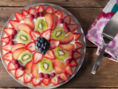 Layer sliced seasonal fruits in concentric circles atop a giant sugar cookie for a sweet take on a pizza pie.
