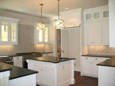 white kitchen cabinets with glass topped uppers. soapstone counters and marble tile backsplash. winning combo!
