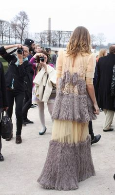 Retro inspired street style. Feathers, pleats and ruffles at Paris Fashion Week.