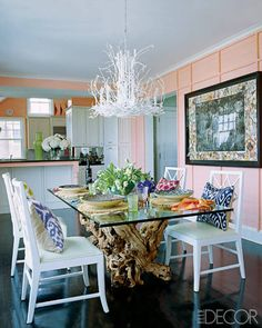Inside a colorful Hamptons home, the dining room's chandelier and chairs are from C. Bell, the grapevine table is by Jayson Home & Garden, and the pillows are by Madeline Weinrib; the hand-colored photograph is by Peter Beard. Tour the rest of the home.   - ELLEDecor.com