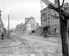 A Cherbourg, rue du Val de Saire, pas très loin de l'Hôpital Pasteur, un soldat américain roule en vélo dans la direction de Tourlaville. Plusieurs immeubles sont en ruines, sur le trottoir d'en face un civil le regarde passer, en arrière plan un groupe d'une dizaine de GI's.