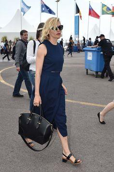 Sienna Miller in navy Victoria Beckham, black leather sandals, and an Alexander McQueen bag.