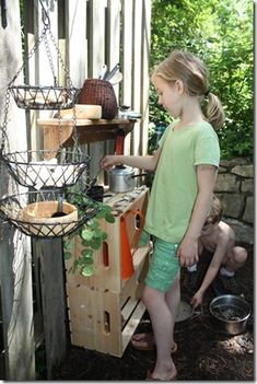 East Side Lawn: Mud pie kitchen.  love the hanging baskets, crates turned on sides for storage