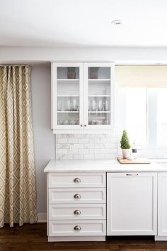 Gorgeous kitchen features glass-front upper cabinets and crisp white lower cabinets paired with white marble beveled subway tile backsplash and white quartz countertops.