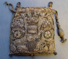 Purse, made of woven silk with gold thread (gold strip wound over silk core) and metal spangles, depicting a lion and a lamb flanked by snails and surmounted by three crowns over a thistle (in the centre), or a rose (at each side). A drawstring with upstanding tassels at the top and a large stiffened tassel of woven fabric at the end of the cords, further cord knots at the bottom corners with remnants of silk tassels. The design is the same on each side and the purse is padded with coarse…
