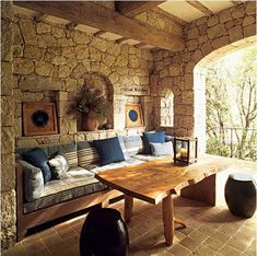 Stone walls, tile floors and built-ins provide a cozy outdoor area for dining and lounging.