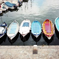 Colorful boats tied to stone dock.