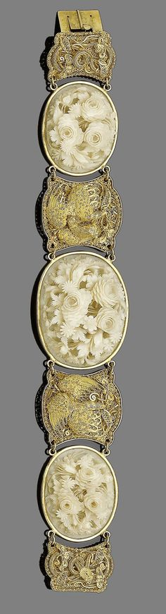 A late 19th century gold and ivory bracelet Set with three oval ivory plaques, each finely carved in high relief depicting floral bouquets, with graduated gold filigree spacers depicting phoenixes and serpents, Chinese maker's mark, retailer's mark W.W