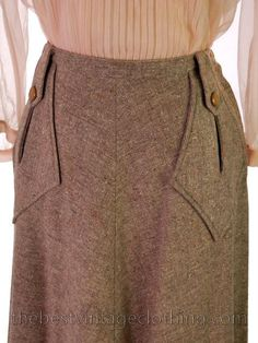 Vintage A line Skirt from the 1940s in a 100% wool taupe tweed with specks of coral beige and brown. The best detail is the great pockets on the front with button tab. It has a side zipper and button