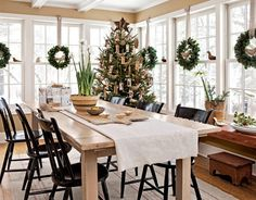 wall to wall windows with wreaths in every one, loads of natural light, black thumb-back chairs, paper whites, and an antique table.