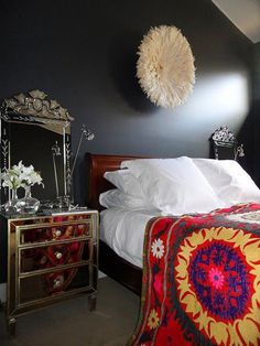 This unusual bedroom design is a mix of global style, tradition and glamour with its mirrored chests, Venetian mirrors, sleigh bed and colorful blanket.