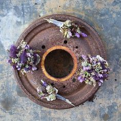 {These corsages and boutonnieres are just hanging out, waiting for their special owners to arrive! I thought they looked cute here on this rusty old wheel bearing dealio.} #graemeandbree #thebarnatthedanapowershouse