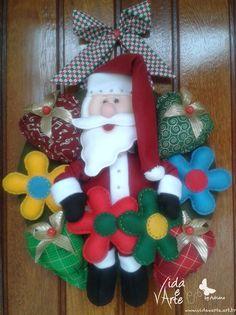Guirlanda de Natal em feltro e tecido trazendo Papai Noel com toda alegria das flores coloridas e todo amor representado através dos corações com laços dourados!