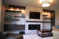 Interior. rectangular black led tv on over black wooden fireplace mantel combined by grey stone fireplace with grey wooden cabinet and wooden board shelf on white wall. Awesome Looks Of Modern Entertainment Centers With Modern Furniture For Your Living Room