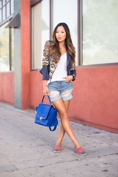 Aimee Song goes laid back with a twist, styling her espadrilles with distressed cutoffs and a colorful textured jacket. Spice up your summer look even more with an unexpected bold bag.