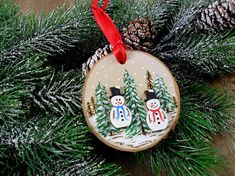 This wood burned birch slice snowman ornament is two dimensional with two snowmen being separate pieces made from birch, painted and attached to the slice. The trees were burned and painted. It has a red satin ribbon hanger. Entirely free hand work and finished with a coating of