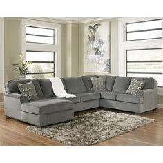 The Loric - Smoke Living Room Collection by Ashley Furniture features the stylish look of sweeping set-back arms along with the welt accented box seating and back cushions surrounded with a soft chenille upholstery fabric creating a beautiful contemporary styled sectional that offers the comfort you deserve.