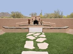 A natural flagstone walkway set in the lawn leads to an outdoor fireplace area. The fireplace design almost resembles the mountain off to the left in the distance. Arizona's Horticulture Unlimited often blends very unique visual effects into their designs. Picture compliments of www.horticultureunlimited.com