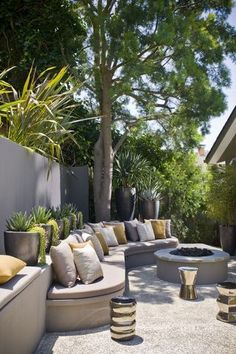 Low maintenance hard-scaping completely softened by the curvature of the seating. Fantastic container lined wall, the perfect backdrop!