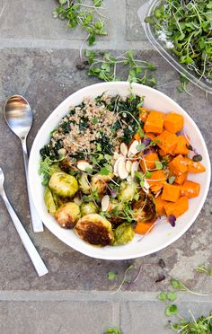 "A ""Buddha Bowl"" is the ultimate satisfying nutritious meal, a bountiful bowl of beautiful, healthy, vegetarian ingredients. This sweet potato brussels sprout buddha bowl combines roasted vegetables kale, quinoa, and a luscious lemony dressing. Plus, it's gluten-free and vegan."
