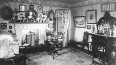 An Edwardian drawing room, with a flower wallpaper border above the picture rail.