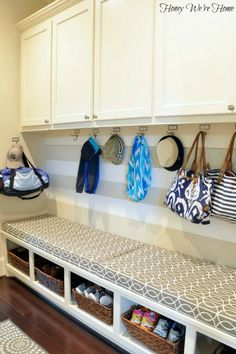 Organized mudroom with bookplate labels and hooks, built-in cabinets and bench seat