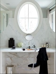 gorgeous marble vanity Love the idea of mirror surrounding the oval window. Natural light is the way to make-up vanity!
