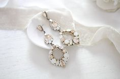 Extra long at 3.5 inches these Swarovski Crystal Bridal chandelier earrings will truly make a statement on your wedding day ! - Handcrafted with CRYSTALLIZED™ - Swarovski Elements stones - Each stone is set by hand in my studio - Swarovski golden shadow, white opal and clear stones - Antique gold finish - Earrings measure 3.5 inches x 1.25 inch - Handcrafted in the US. - Nickel free and hypoallergenic This is an original design by © Treasures by Agnes