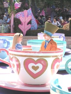 Alice and the Mad Hatter having a chat in a teacup.
