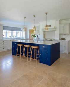 This large kitchen island has bar stool seating and storage. The other side features a bottle rack, appliances and more storage.