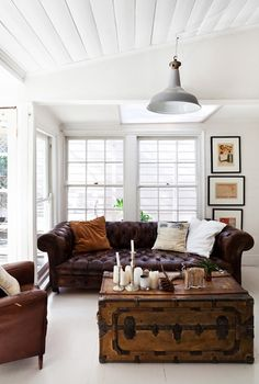 Collected Casual. Leather sofa in simple white living room. Wooden antique shipping box/trunk coffee table. Down & Out Chic