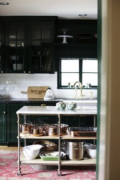 dark green cabinets, rug in kitchen, this bakers rack/island