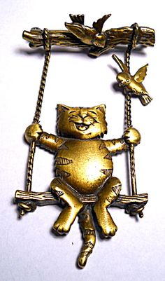 Cat on a swing design vintage brass or bronze brooch or pin with a happy cat on a swing with two birds with brushed and polished bronze finish. It is an unusual piece, and measures approximately 3 by 1 1/2 inches and is in excellent condition. It has 'JJ' manufacturer's markings and a regular locking pin attachment on the back. Interesting and rare piece for discriminating cat costume jewelry collectors! Price is $29.50.