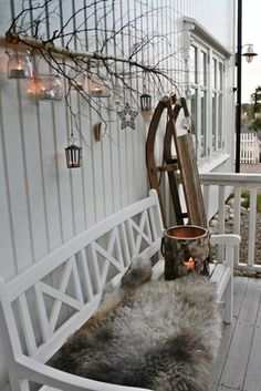 Winterliche Dekoidee für Draußen mit weißer Bank, Fell, Schlitten, Holzwindlicht und kleiner Deko. 1A Outdoor Dekoration.