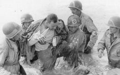 Utah Beach, Navy Hospital Corpsmen and 1st ESB medics evacuate a wounded soldier to a landing craft. Picture taken during D-Day, June 6, 1944.