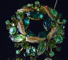 """1970s Costume Jewelry West Germany Retro Brooch ~ Shades of Green Gorgeous vintage pin /brooch Navette Cabochon stones interchanging with rhinestones in various shades of green. Excellent condition with clear stones Hallmarked made in Germany West 2 1 /8 x 2 x ½"""""""