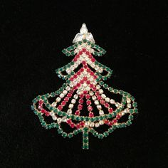 Vintage Christmas tree brooch You have just found STUNNING at a reasonable price! This brooch is gorgeous and in impeccable vintage condition.  Notice the solid gold tone soldering on the back. The skirt of the tree dangles and moves slightly back and forth allowing the green, red and clear rhinestones (all intact) to sparkle like crazy.  No markings. This one might just have to stay with me...  (JEFFHWY) Vintage Jewelry Brooches