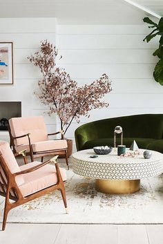 Traditional deep-olive-green, velvet sofa meets mid-century 'millennial pink' side chairs, together with a Moroccan-inspired round pedestal coffee table for a spirited eclectic convergence.