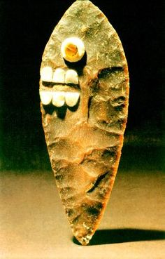 The personified flint knives with faces on both sides were symbolic of sacrifice. This particular knife is decorated with applied pieces of turquoise, obsidian, and shell arranged as teeth and eyes on a painted blade. Knives were recovered from Offering 52 on the Huitzilopochtli side of the Templo Major.