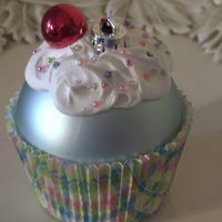 Super Easy Cupcake Ornament- Large ball ornament glued into a cupcake liner, Gesso for frosting, seed beads for sprinkles and a mini red ball ornament for the cherry!