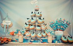 Shark party -- love the colors, shark fin cupcakes, and gummy skewers. See website for cute photo op and homemade shark fin favors.