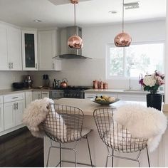 Beautiful modern day kitchen! Love the rose gold lights and the bar stools
