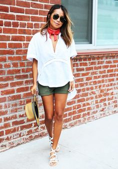 A white top is worn with green shorts, white gladiator sandals, straw hat, bandana as scarf and aviators.