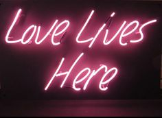 'Love lives here' Neon sign