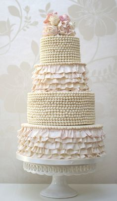 a gorgeous wedding cake with ruffles and pearls