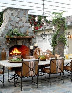 Stone patio with table and stone fireplace.