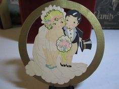 1920's Gibson die cut bridge tally card with cherubic bride and groom inside gold gilded circle unused. $9.50, via Etsy.