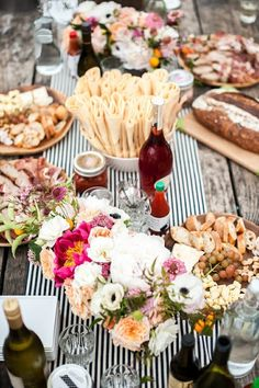 Summer outdoor entertaining alfresco dinner party lunch with antipasto platters, artisan bread, wine, flowers, black white striped table cloth table runner
